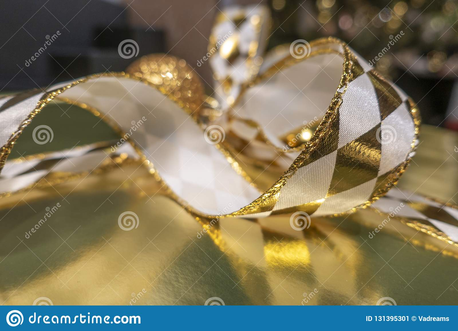 Abstract image christmas gift with shiny gold ribbons and bokeh background