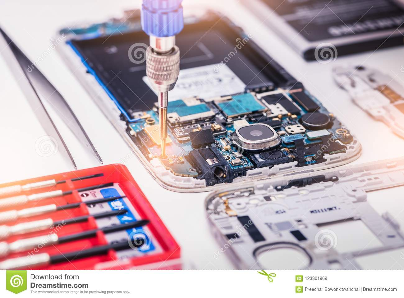 The abstract image of the technician assembling inside of smartphone by screwdriver in the lab.