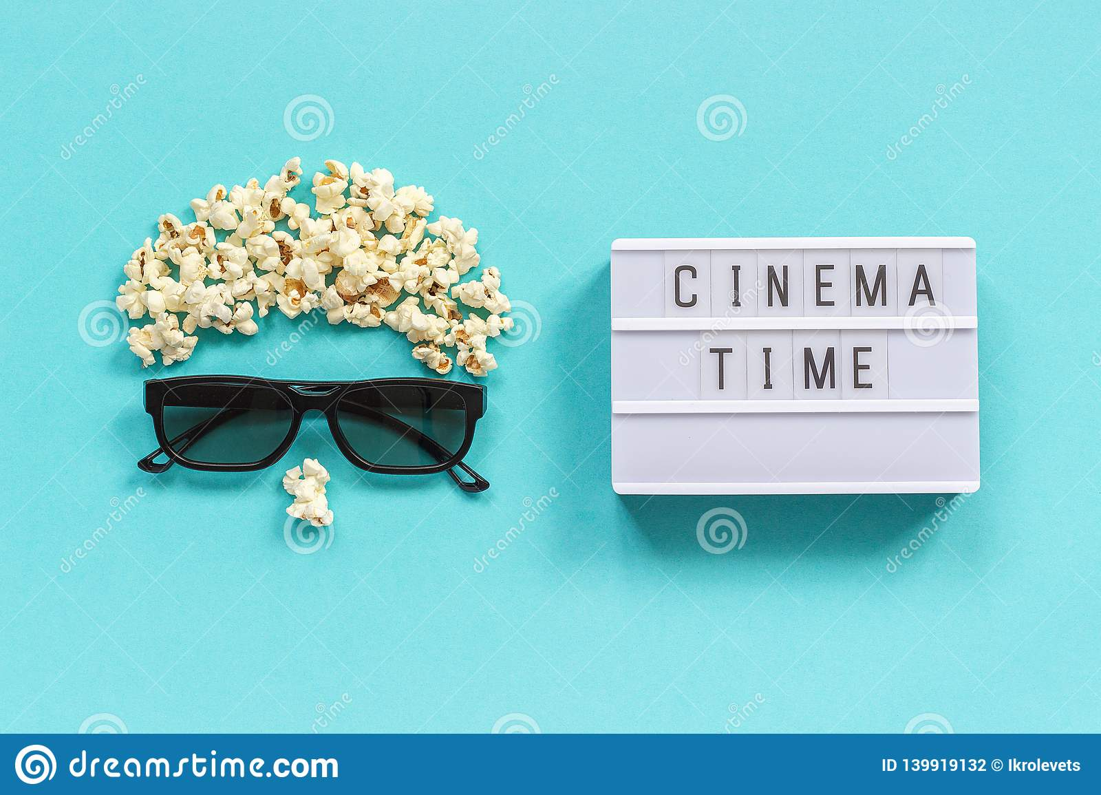 Abstract image of viewer, 3D glasses, popcorn and light box text Cinema time on blue paper background. Concept cinema movie and