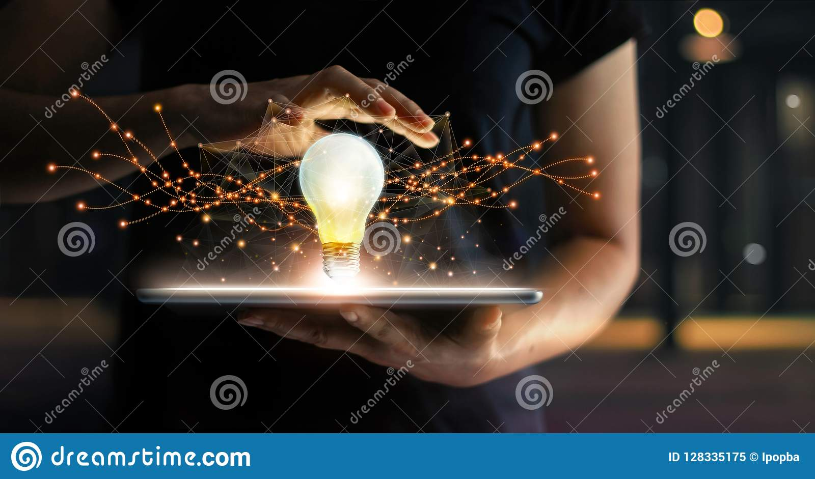 Abstract. Innovation. Hands holding tablet with light bulb future