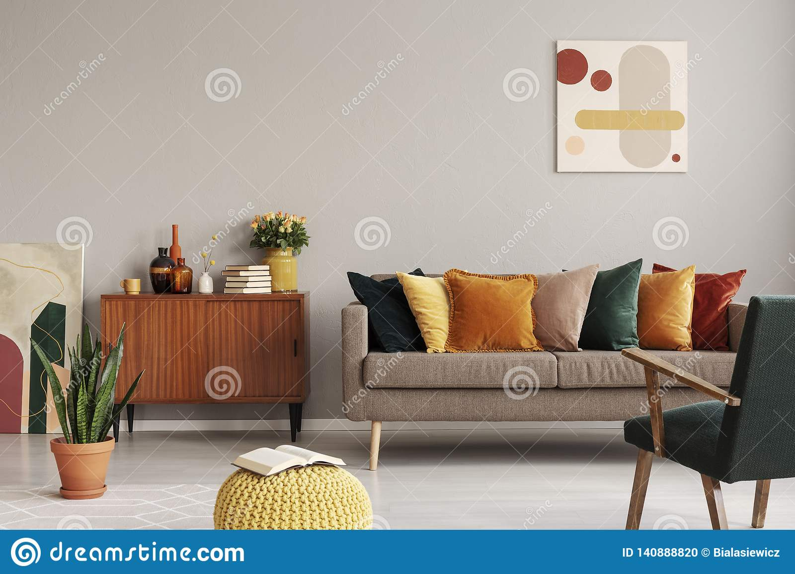 abstract painting on grey wall of retro living room interior with beige sofa with pillows