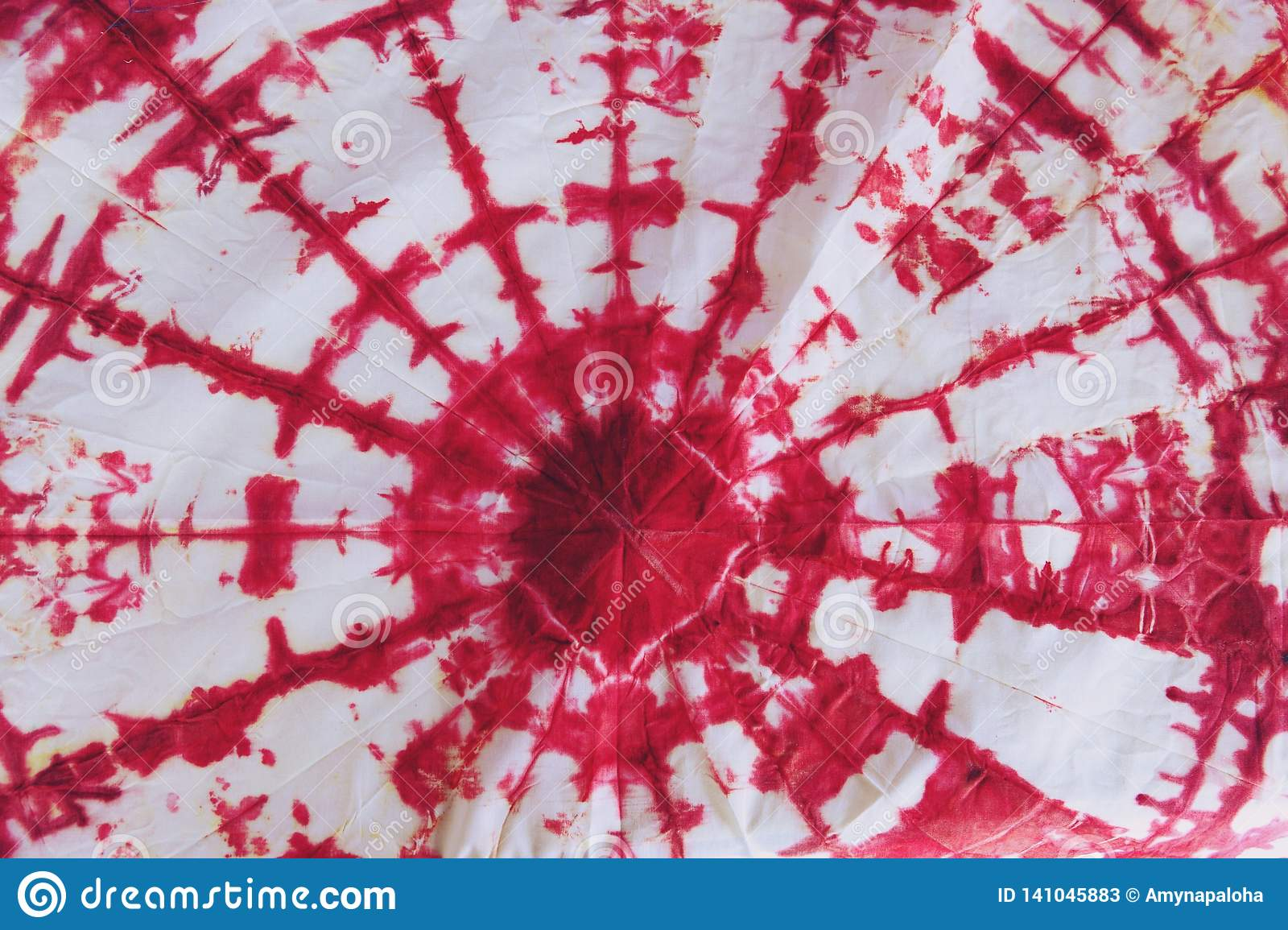 Abstract tie dyed fabric of red color on white cotton