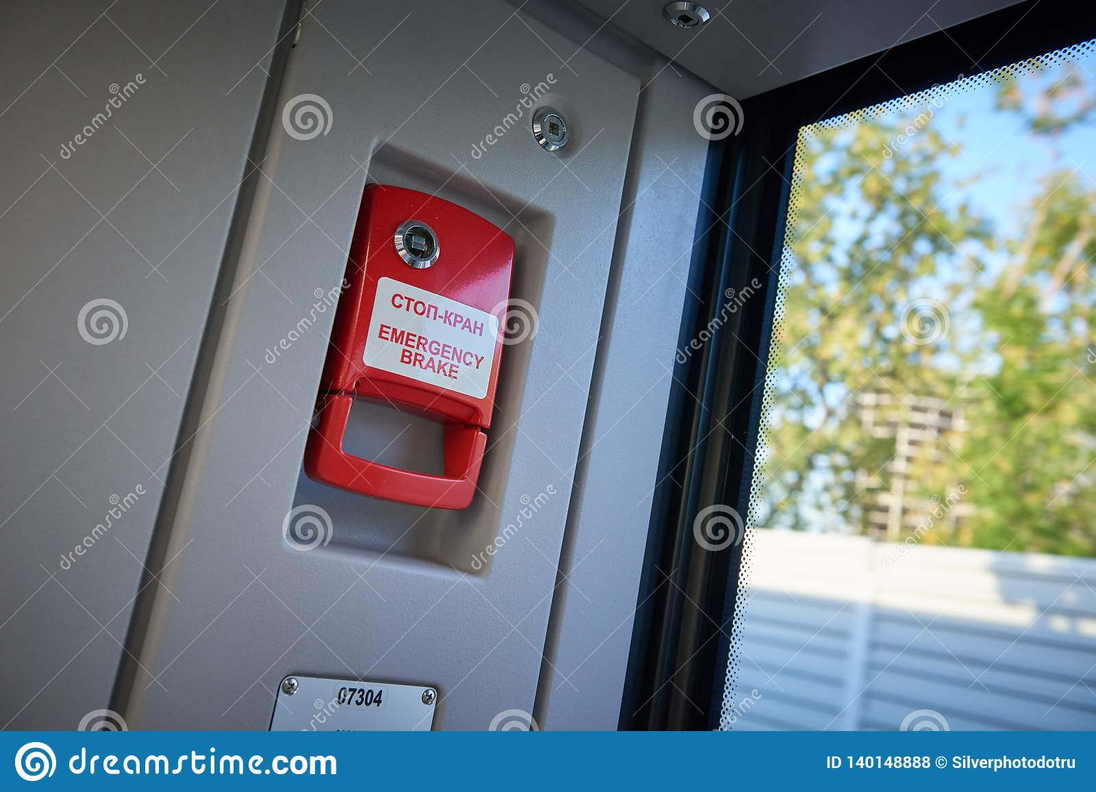Abstract view on red emergency brake handle near to automatic doors in the new modern European passenger train. Passenger and trai