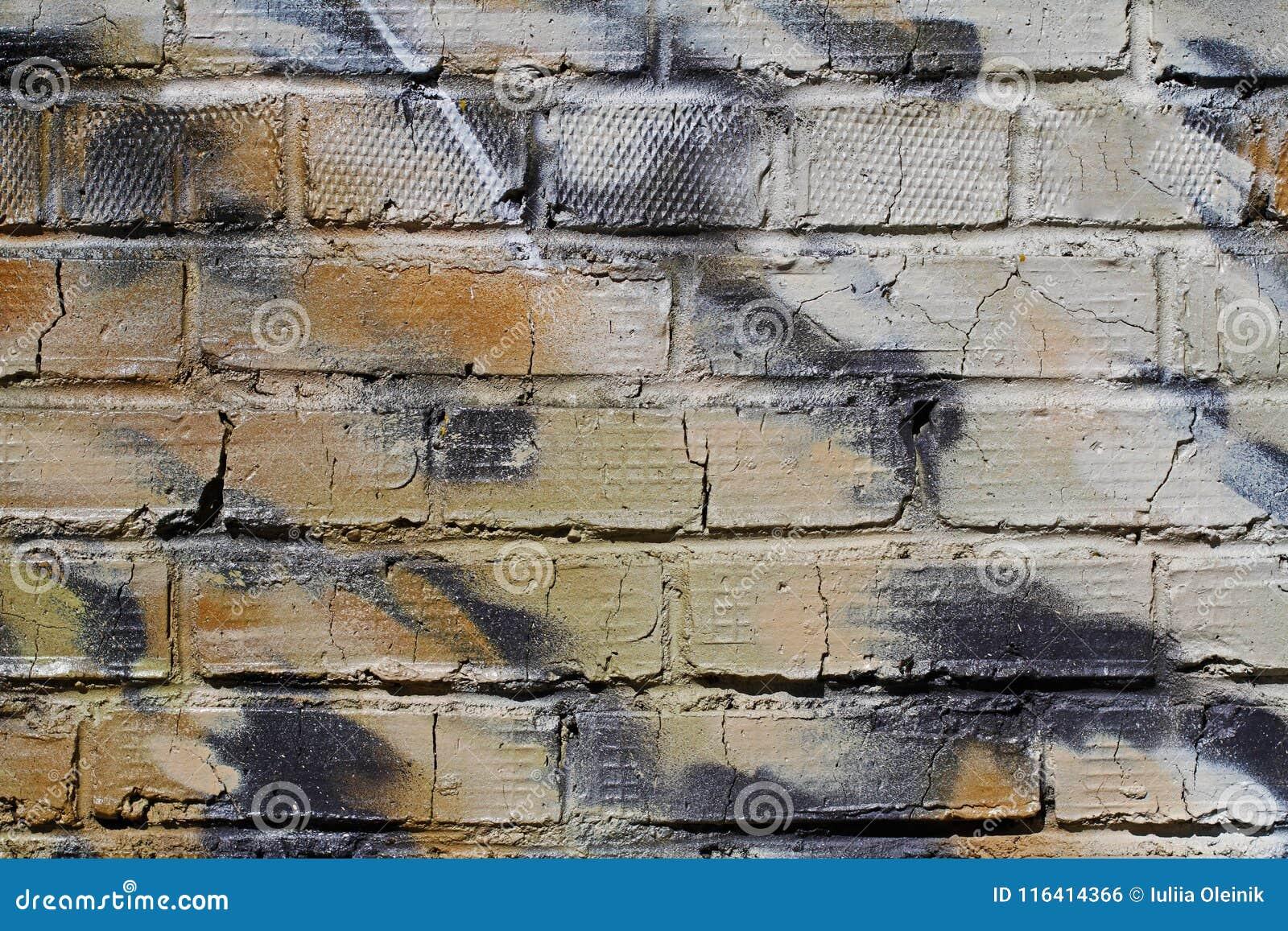 Abstracte kleurrijke groene, witte, beige en zwarte bakstenen muur met barsten