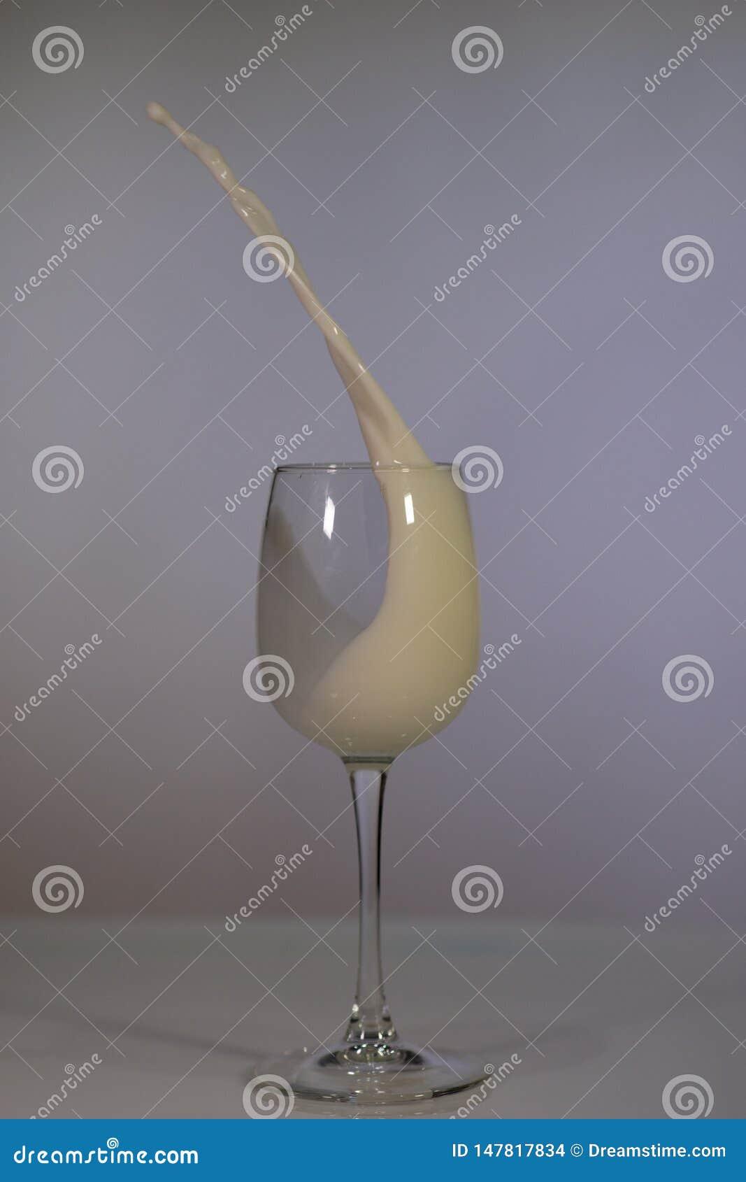 Glass of milk on a dark background. Spilled milk. Dairy produce.