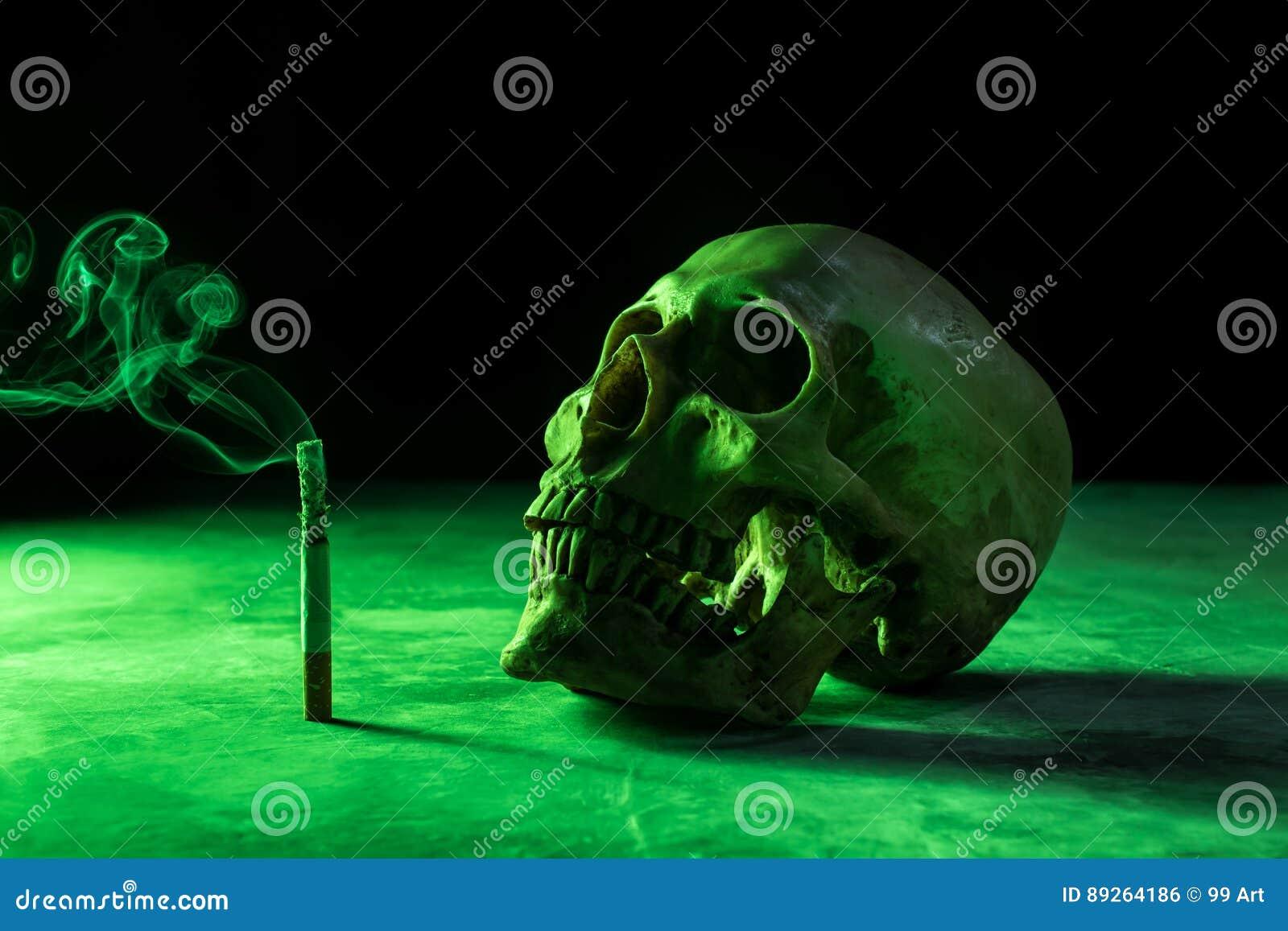 Abstraia o crânio imóvel da vida de um esqueleto com cigarro ardente,