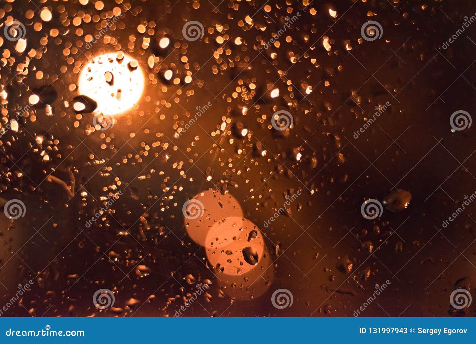 Abstraiga el fondo Descensos sobre el vidrio en la noche con el bokeh