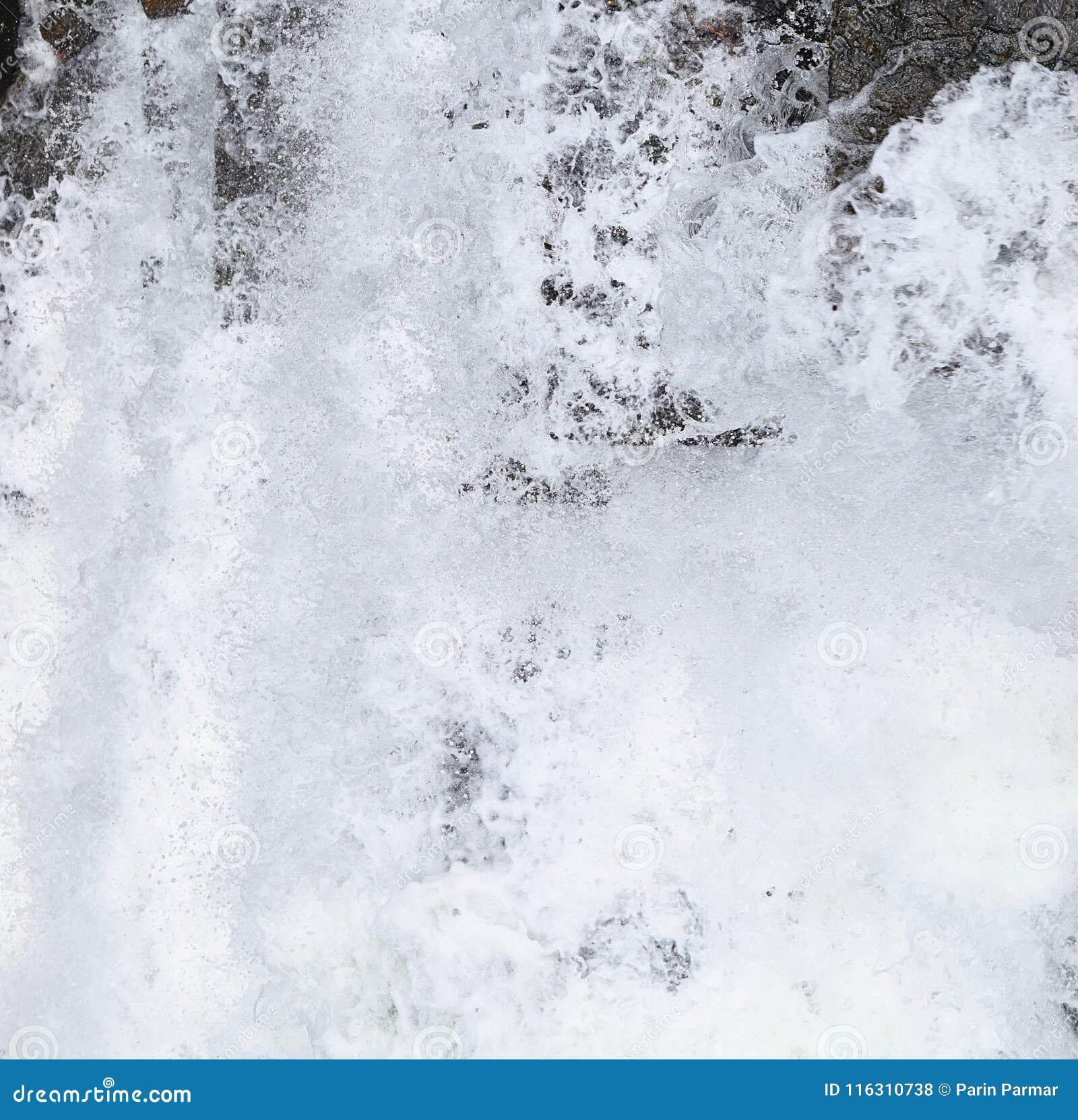 Abstrakt bakgrund - stänk av vitt skummande vatten mot skuggor av grå färger och svart