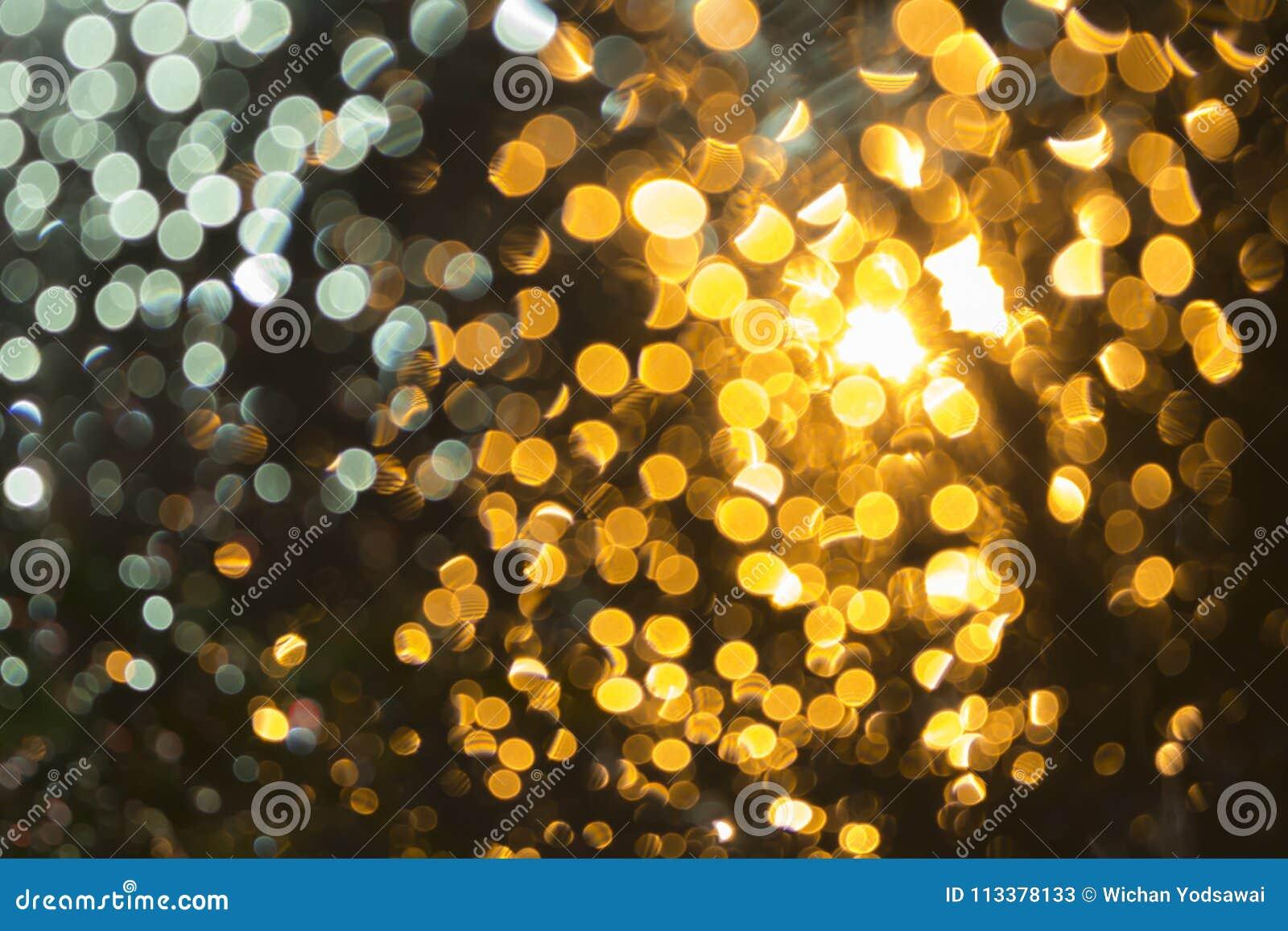 Abstrakt bokeh: Ljust suddigt för bakgrund, apelsin från vattensmå dropparna, framdel av bilen