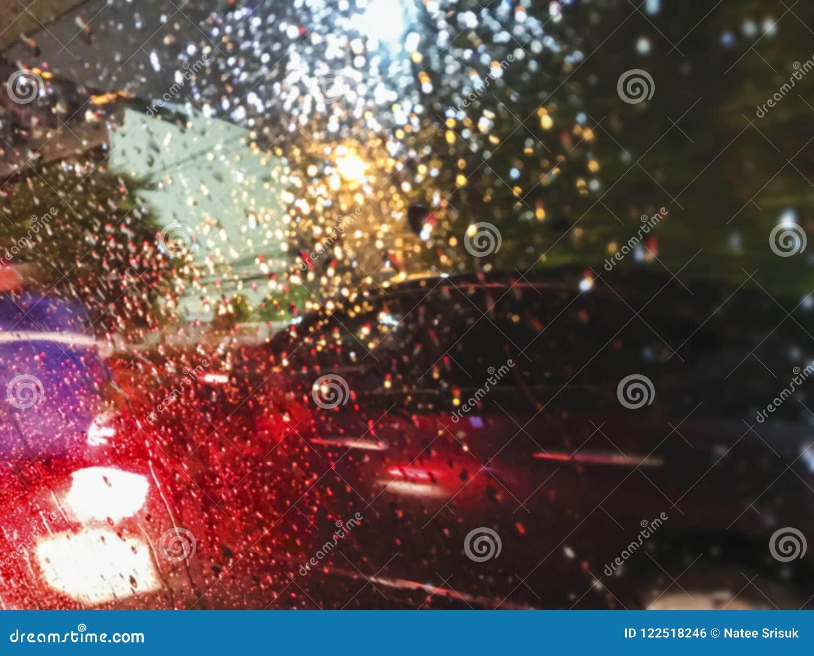 Abstrakt suddig bakgrund av nattljus i regnig dag