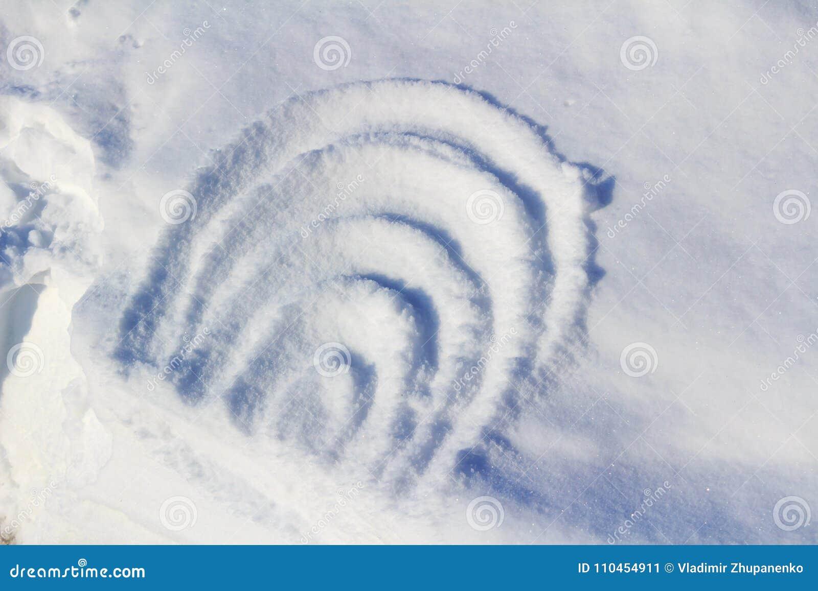 Abstrakt teckning på snö på en solig vinterdag
