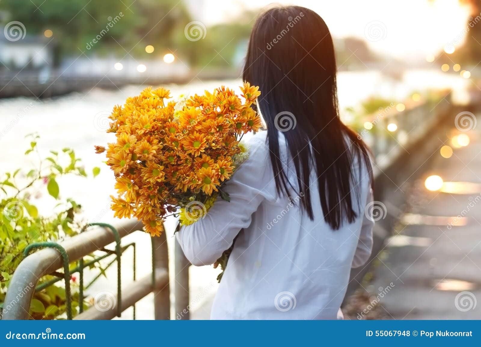 Abstrakte Frau mit Blumenstrauß blüht vibrierendes in den Händen auf Straße und Kanal