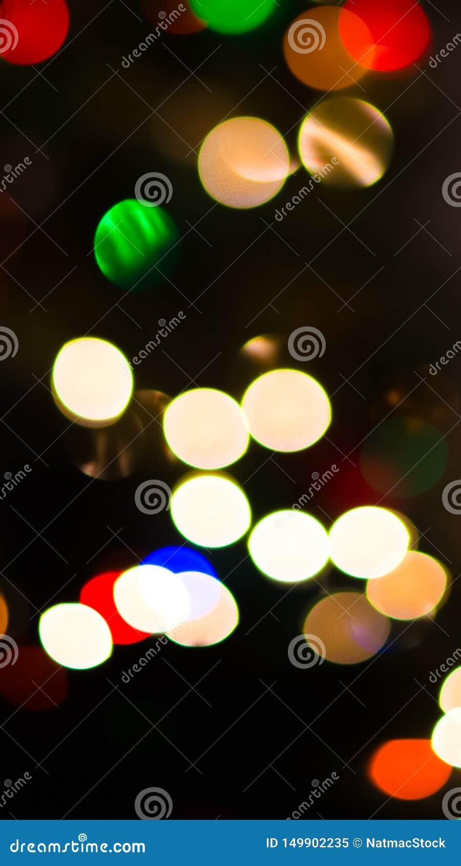 Abstrakter Hintergrund der Christbaumkerzen - dunkel mit Kreisen des Lichtes in den verschiedenen Farben