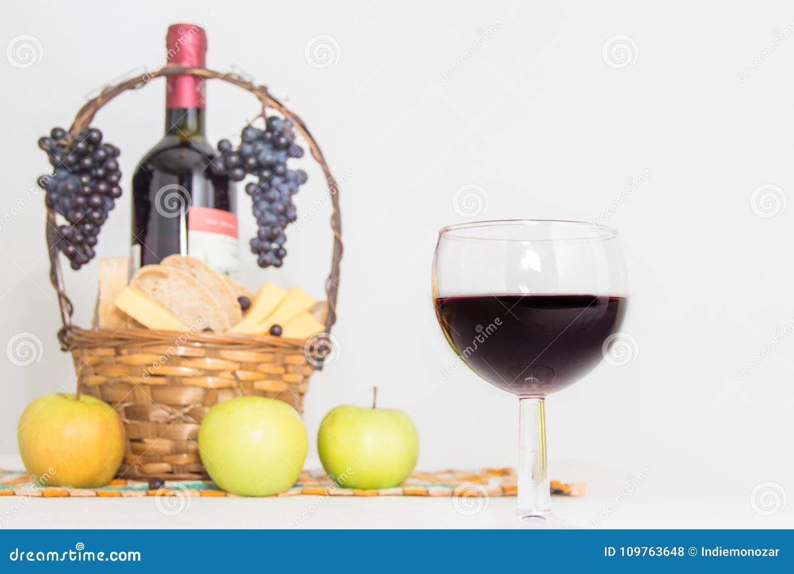 Abstraktes Bild eines Glases Weins Eine Flasche des Rotweins, der Trauben und des Picknickkorbes mit Käse und Brotscheiben