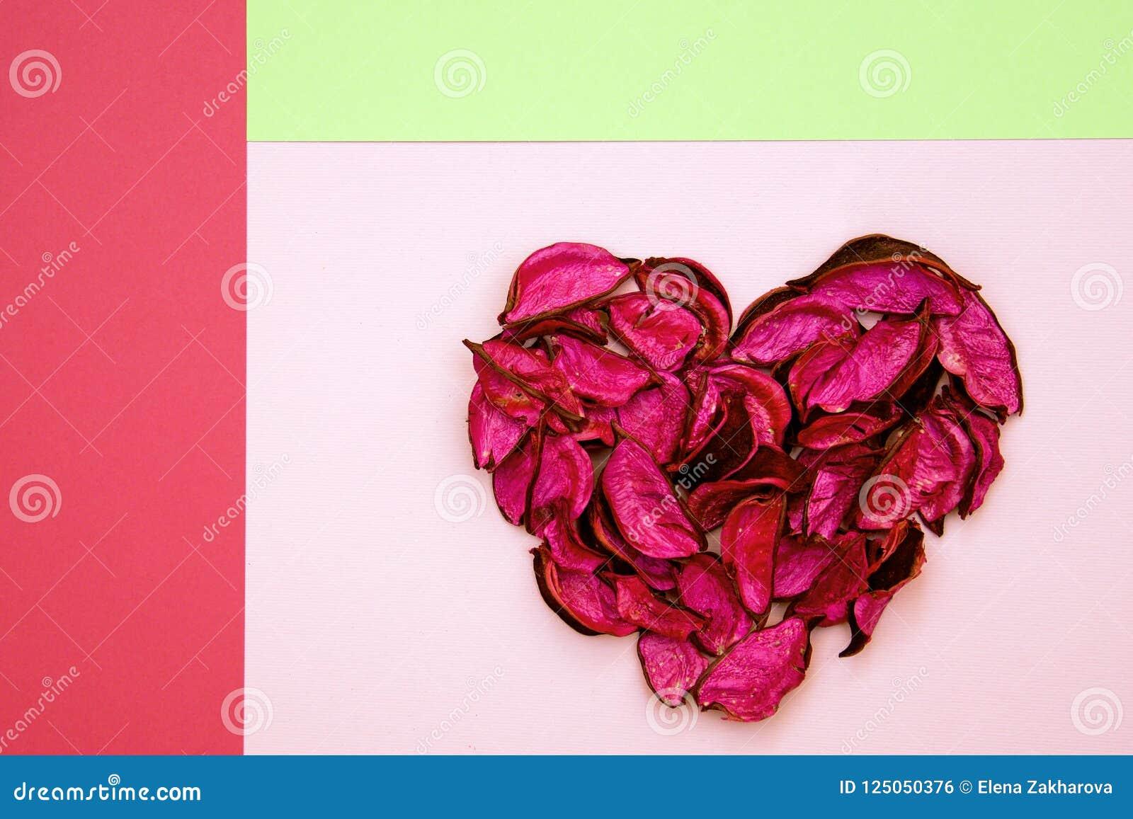 Abstraktes Herz gemacht von getrockneten Blumenblättern auf buntem geometrischem Hintergrund