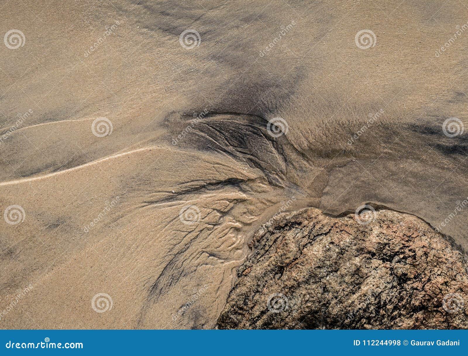 Abstraktes Muster auf dem Strandsand