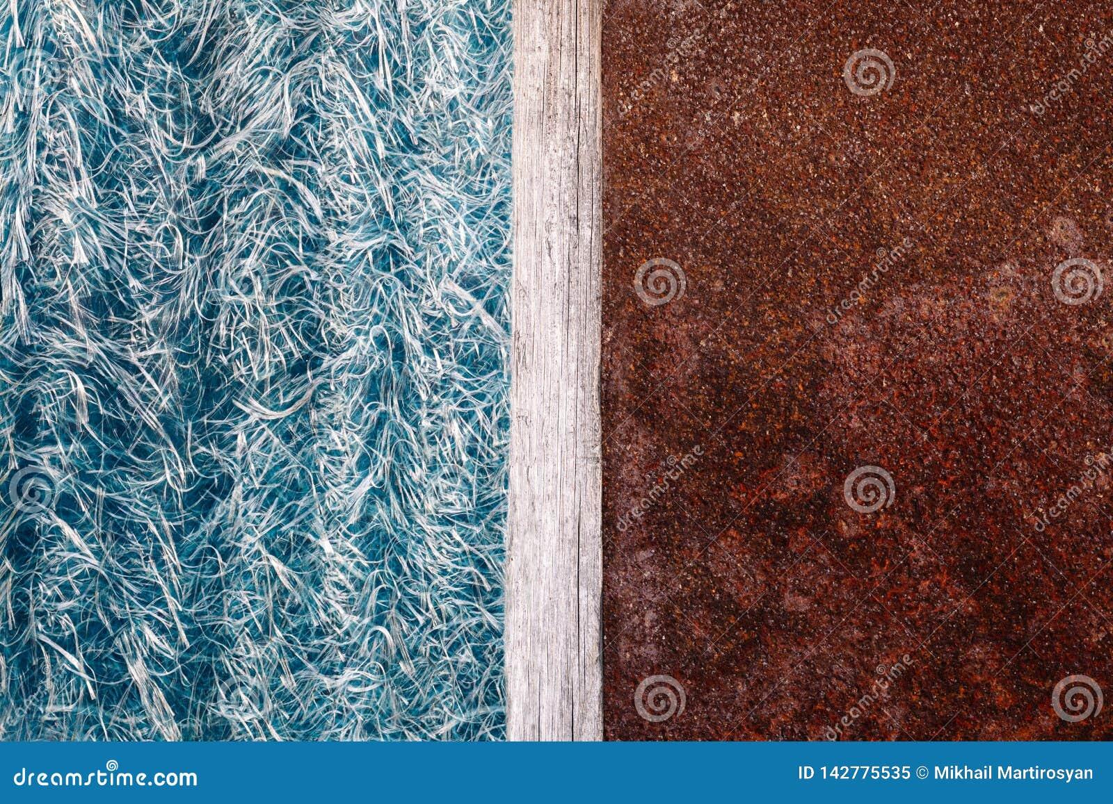 Abstraktionen av blå textolite kritiserar, bakgrund i halva med en rostig metallplatta och en delande remsa av trä