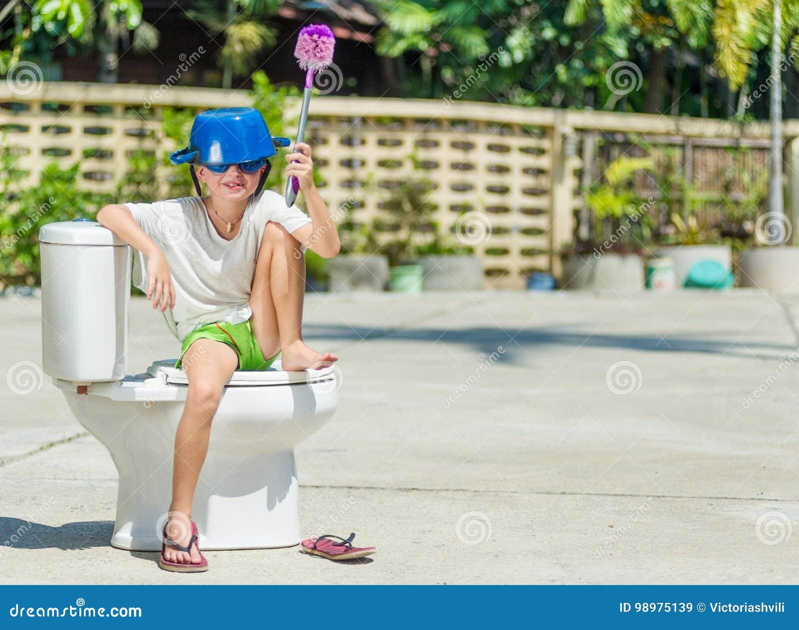 Absurd beeld: leuke jongen die in beschermende brillen op het toilet zitten, dat