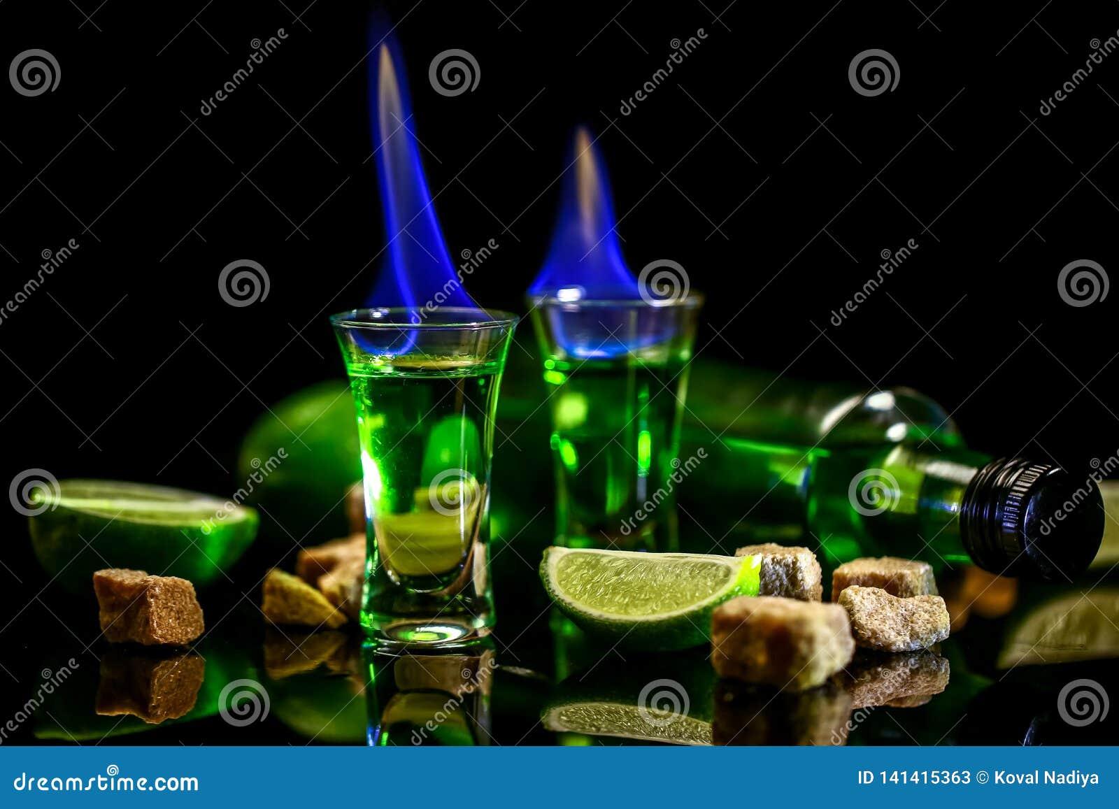 Absynt w szkle z wapno plasterkami na ciemnym tle Butelka absynt i szkła z paleniem sześcianu brązu cukier wolna przestrzeń