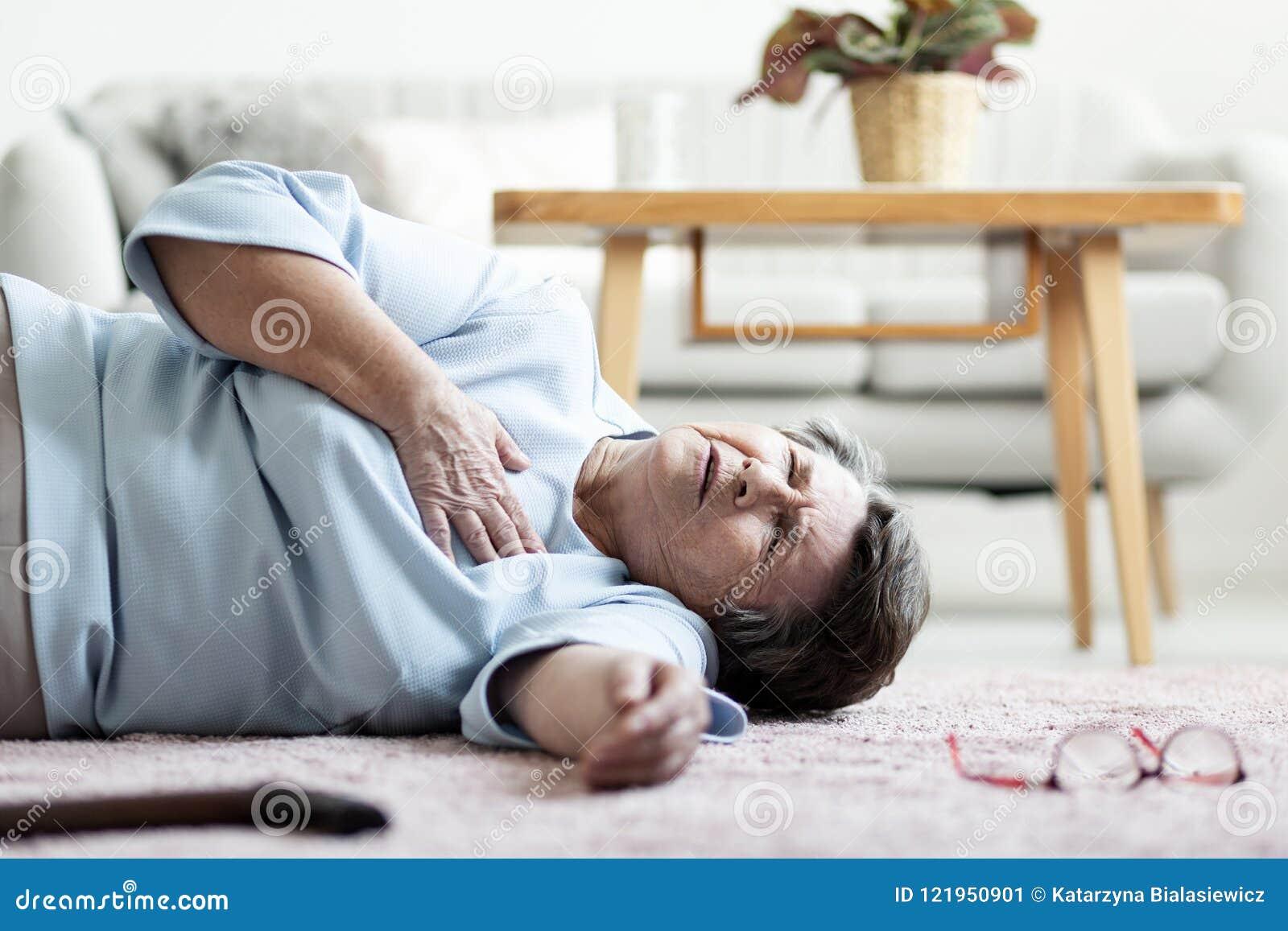 Abuela con el ataque del corazón que miente en el piso solamente