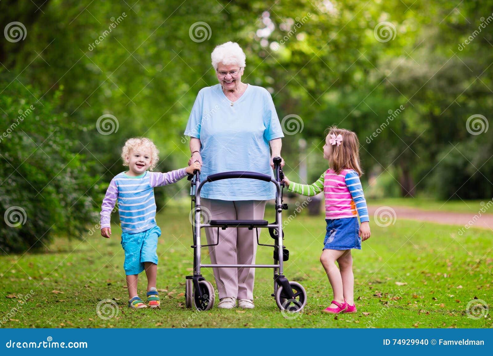 Abuela con el caminante que juega con dos niños