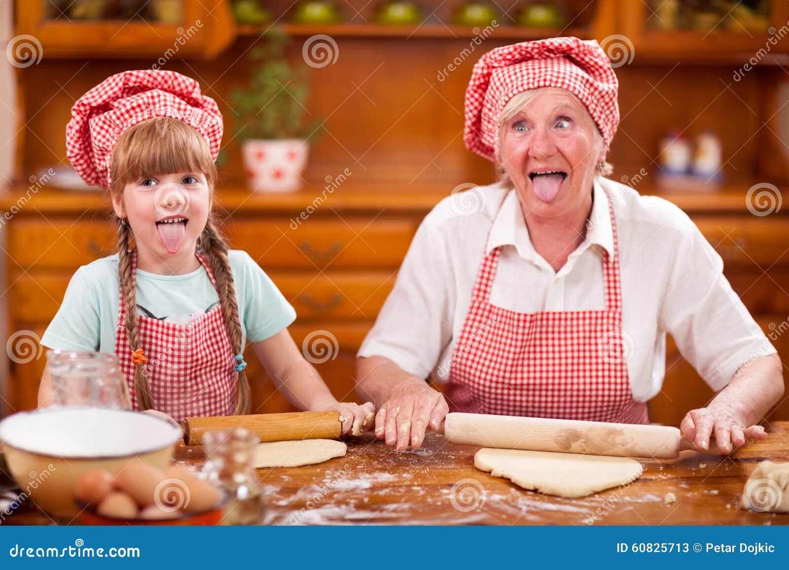 Abuela divertida y pequeño lollygag de la nieta en el kitch
