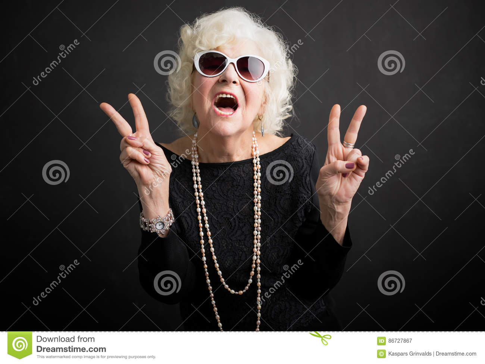 Abuela fresca que muestra el signo de la paz