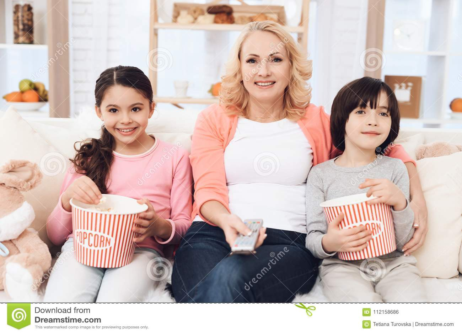 Abuela hermosa joven con sus nietos que comen las palomitas y que miran película en casa en el sofá