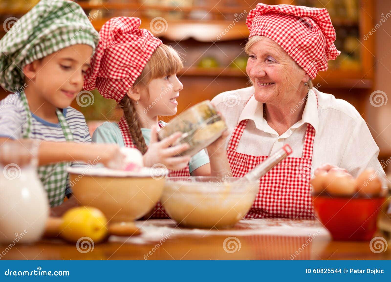 Abuela, nieto y cocinero Baking In Kitchen de la nieta