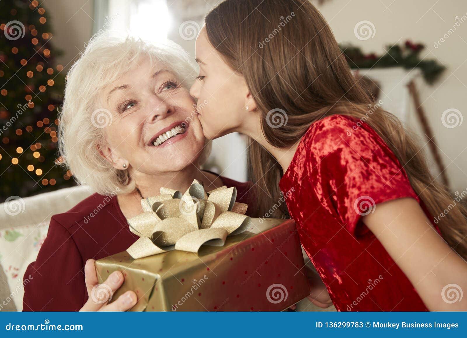 Abuela que recibe el regalo de la Navidad de nieta en casa