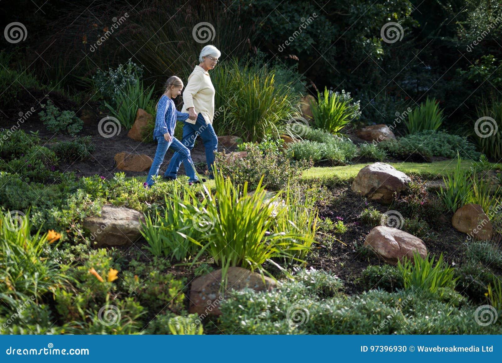 Le Jardin De Grand Mere abuela y nieta que caminan en el jardín foto de archivo