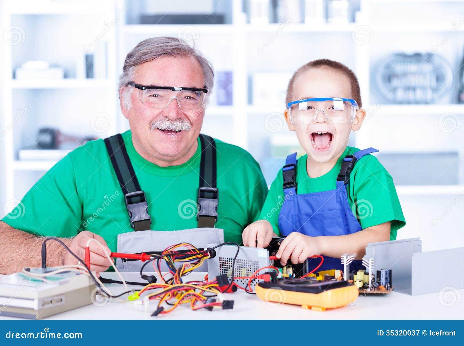 Abuelo feliz y nieto que trabajan en taller