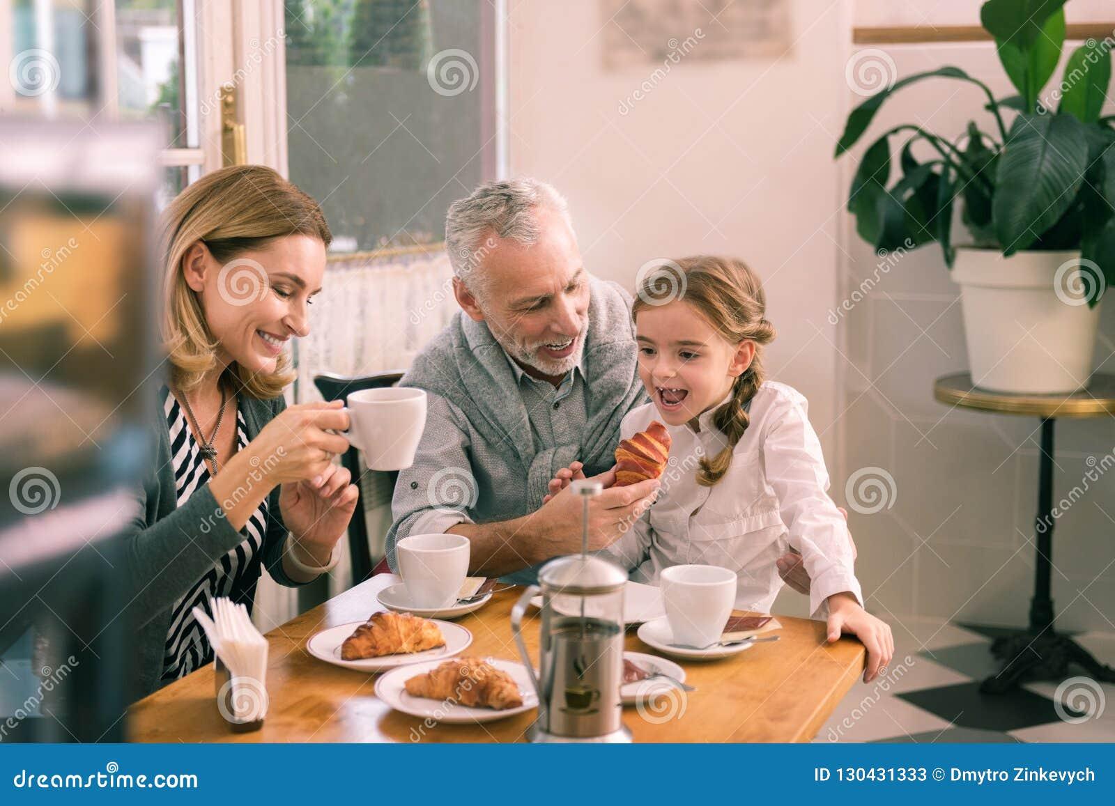 Abuelo gris-cabelludo sonriente que da a cruasán su niña
