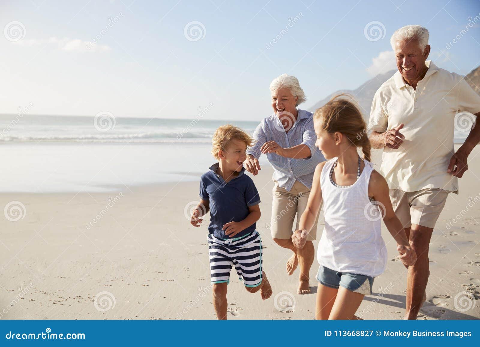 Abuelos que corren a lo largo de la playa con los nietos el vacaciones de verano
