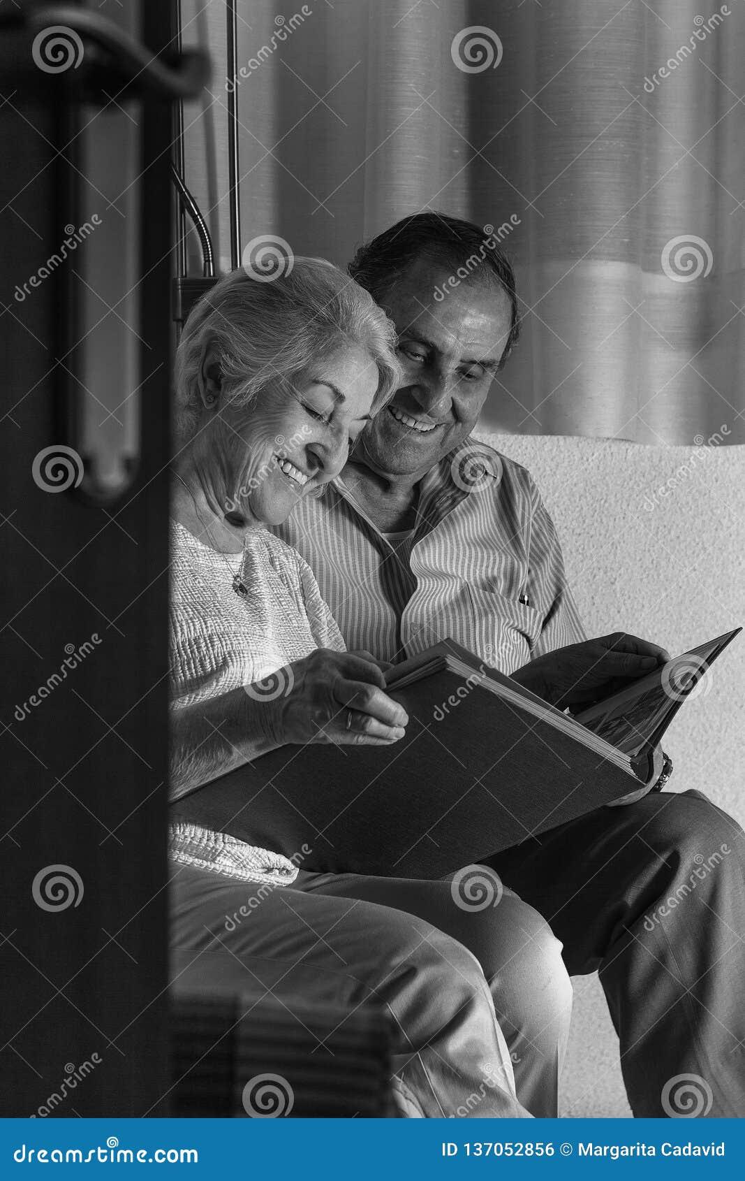 Abuelos que revisan su álbum de las fotografías de la familia