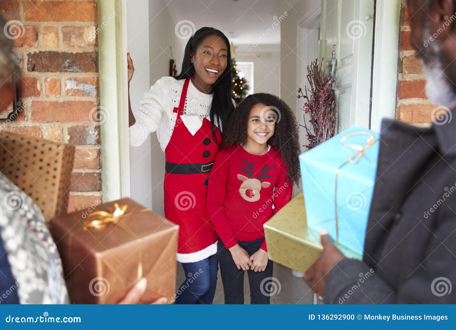 Abuelos que son saludados por la madre y la hija como llegan para la visita el día de la Navidad con los regalos