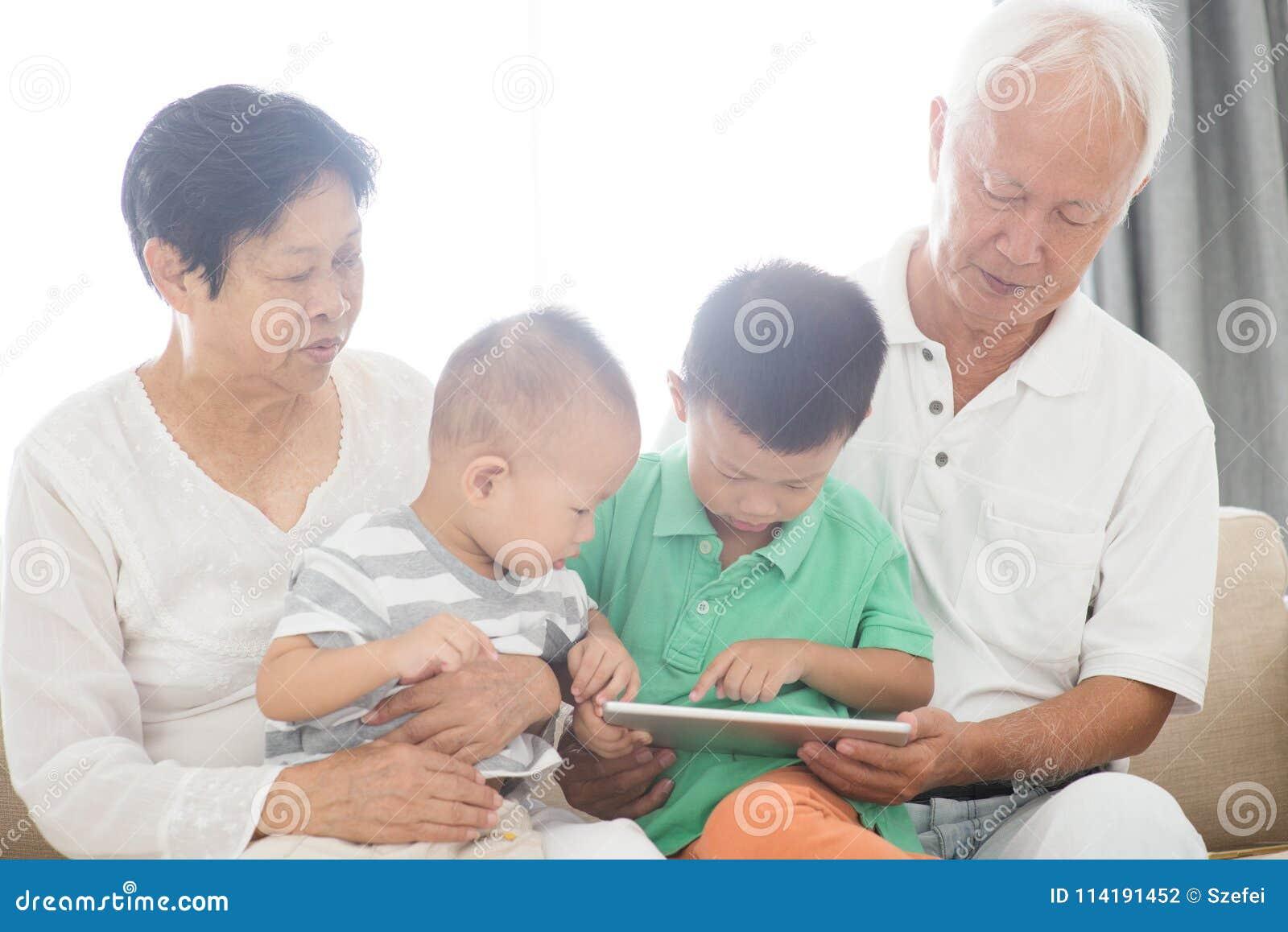 Abuelos y nietos que usan la PC de la tableta