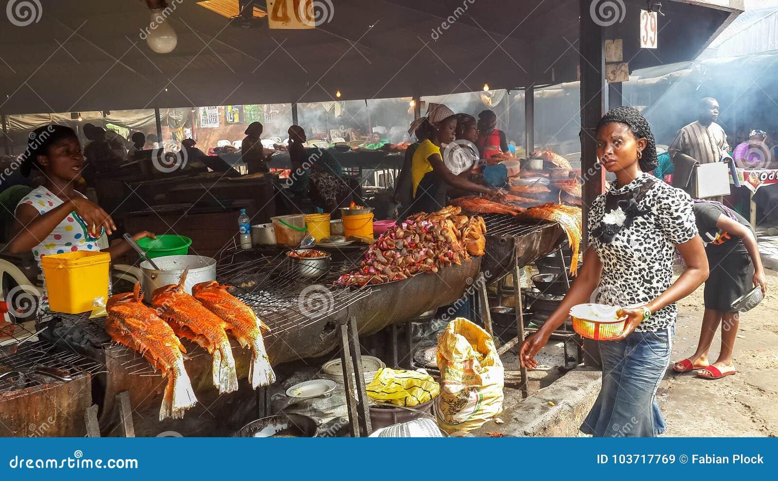 ABUJA, NIGÉRIA, ÁFRICA - 3 DE MARÇO DE 2014: Mulheres africanas não identificadas que preparam peixes e o outro alimento no merca