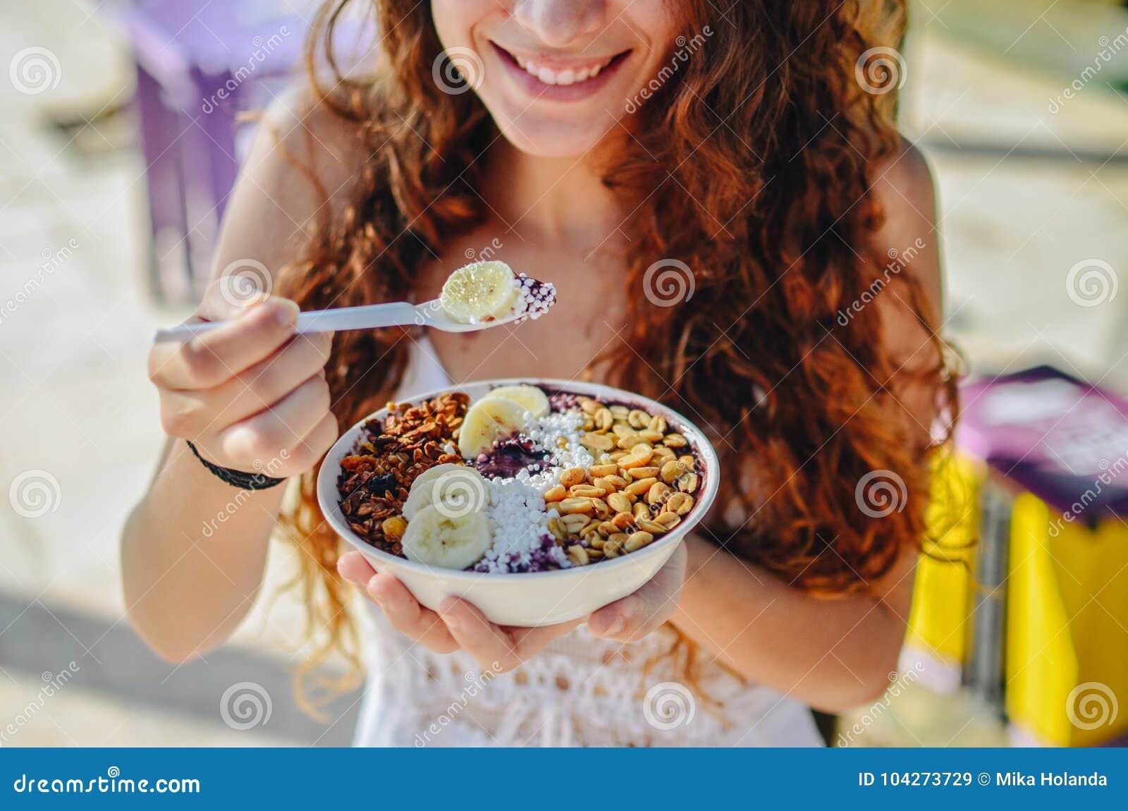 Acai吃早晨早餐的碗妇女在咖啡馆 果子圆滑的人健康饮食特写镜头减重的用莓果和燕麦粥