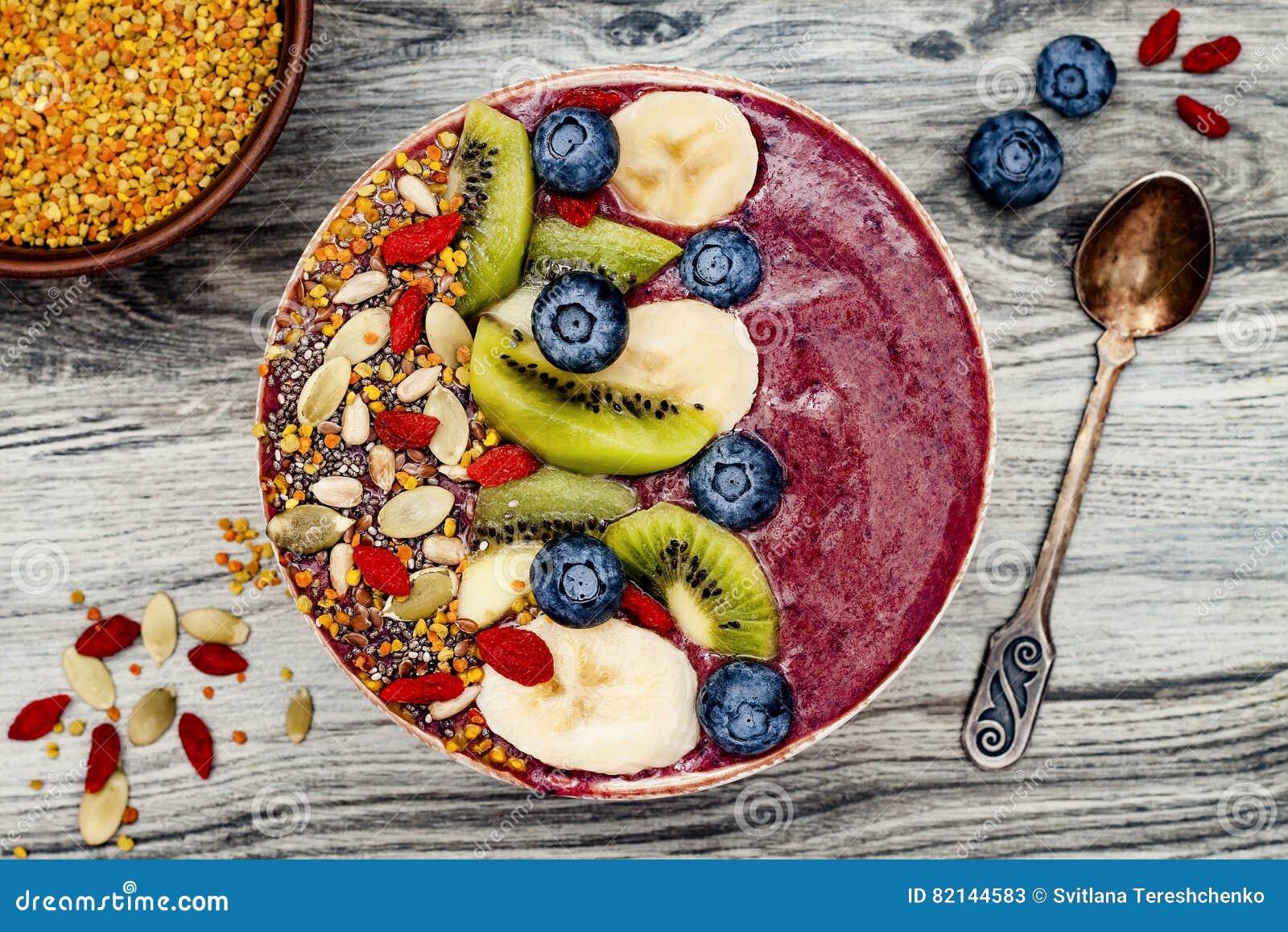 Acai早餐superfoods圆滑的人滚保龄球与chia种子、蜂花粉、goji莓果顶部和果子 顶上 顶视图,平的位置