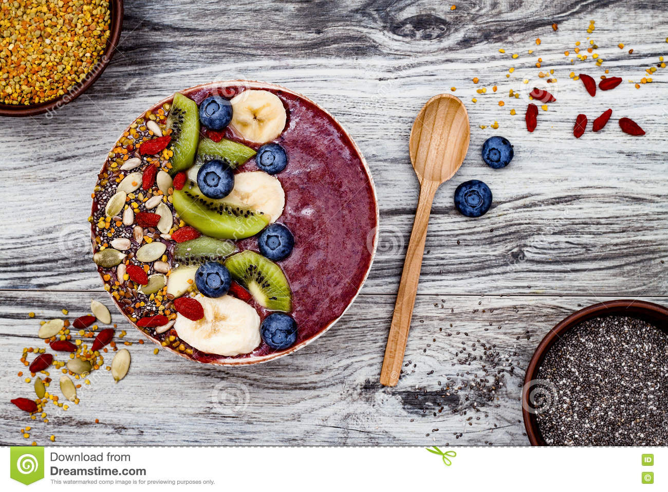 Acai breakfast superfoods smoothies bowl with chia seeds, bee pollen, goji berry toppings and fruits. Overhead. top view, flat lay