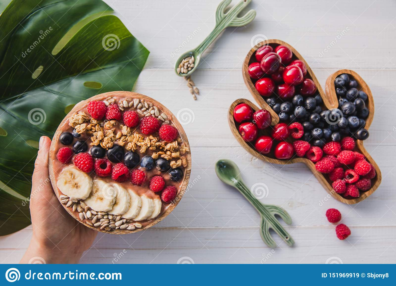 Acai smoothie, granola, seeds, fresh fruits in a wooden bowl in female hands with cactus spoon. Plate filled with