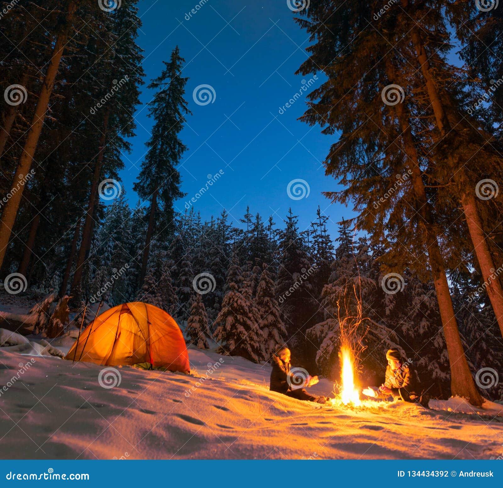 Acampamento com ar livre da fogueira e da barraca no inverno