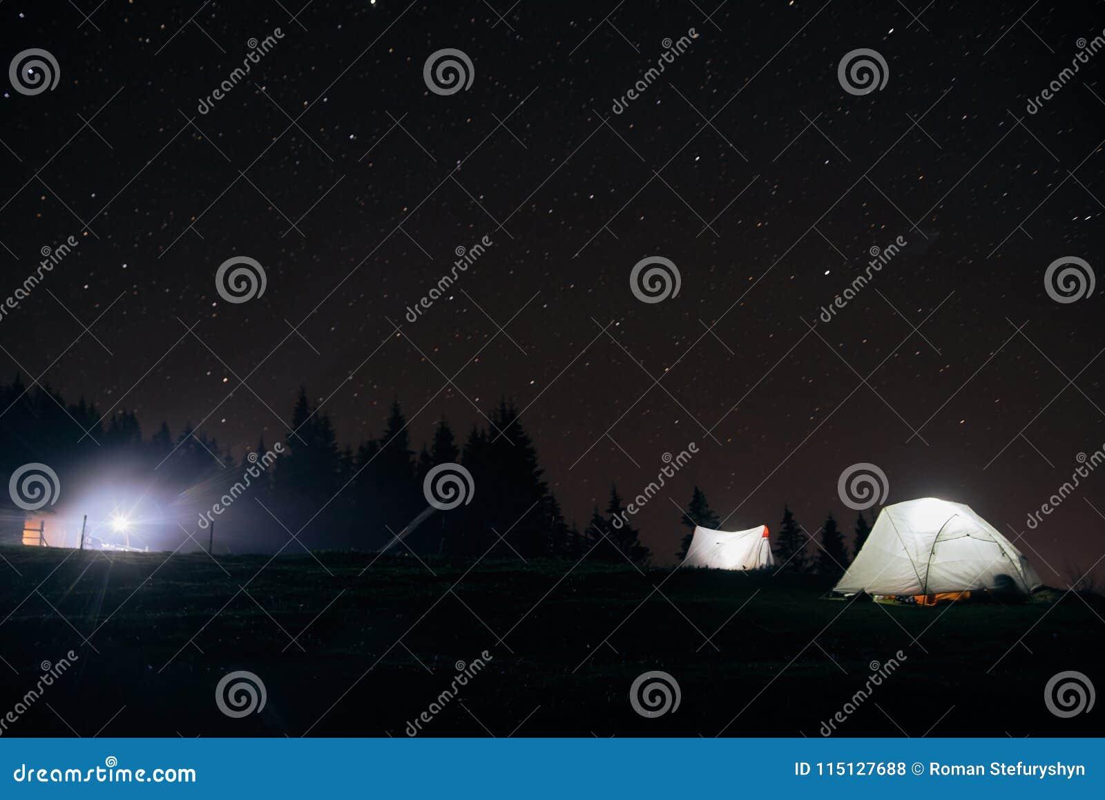 Acampando debajo de las estrellas en la noche en montañas, tiendas iluminadas