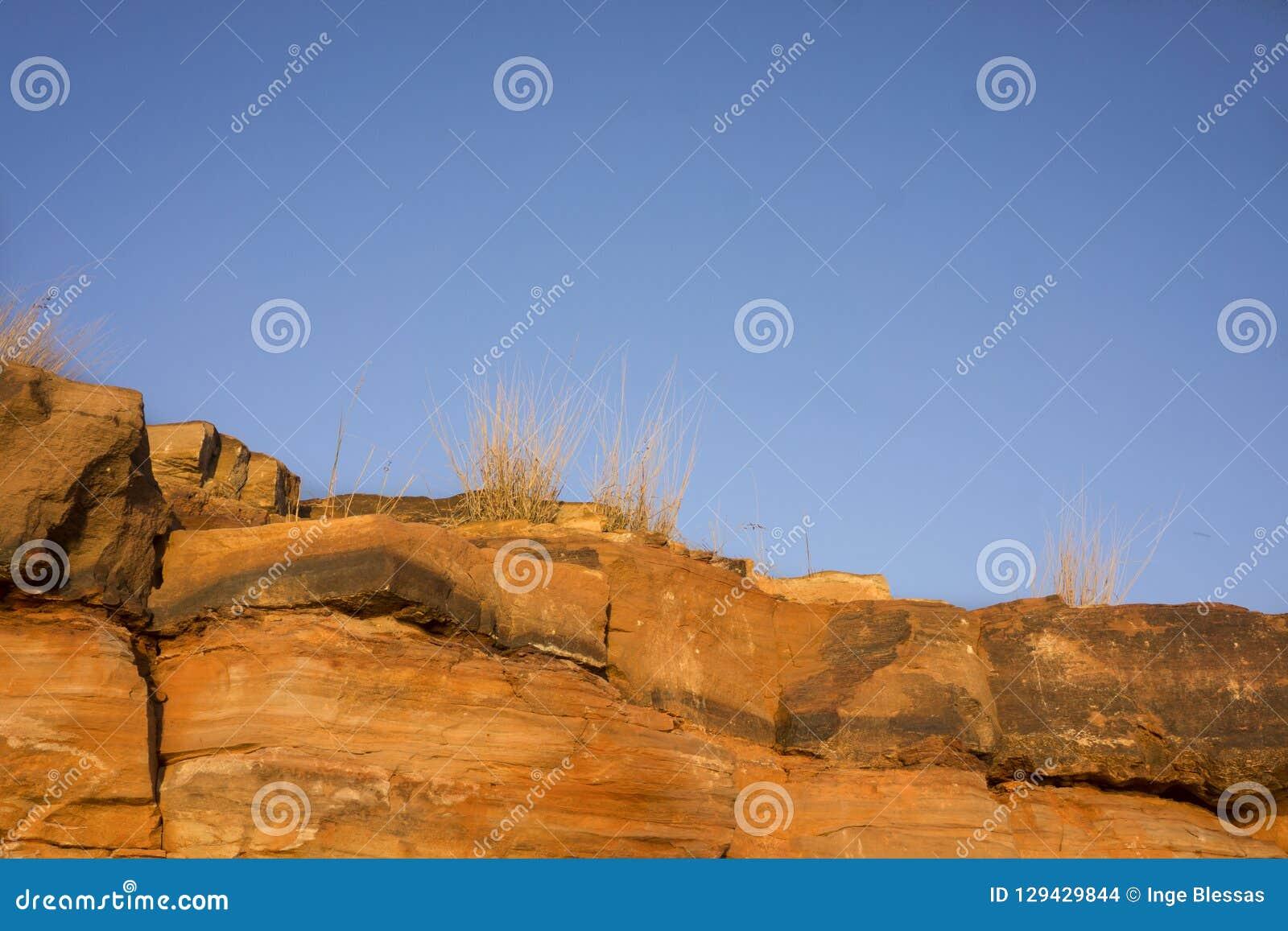 Acantilados de oro de la piedra arenisca encendidos por puesta del sol