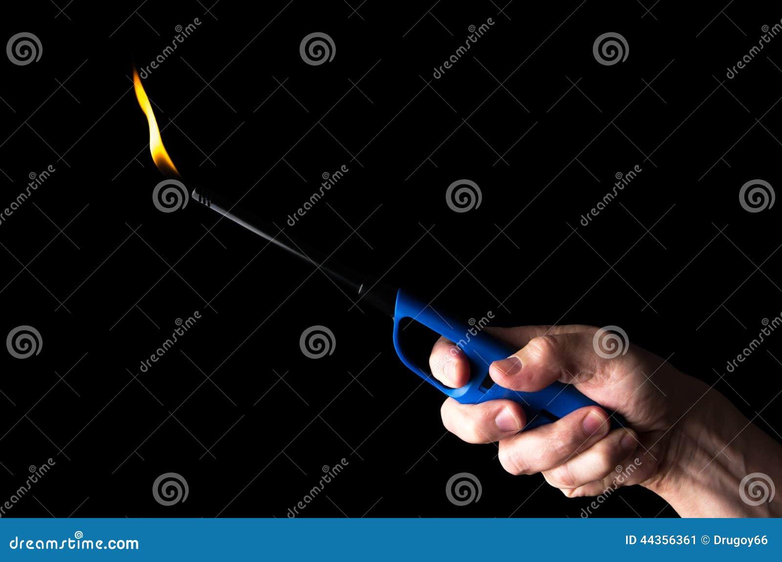 Accendino di gas bruciante in mano di un uomo