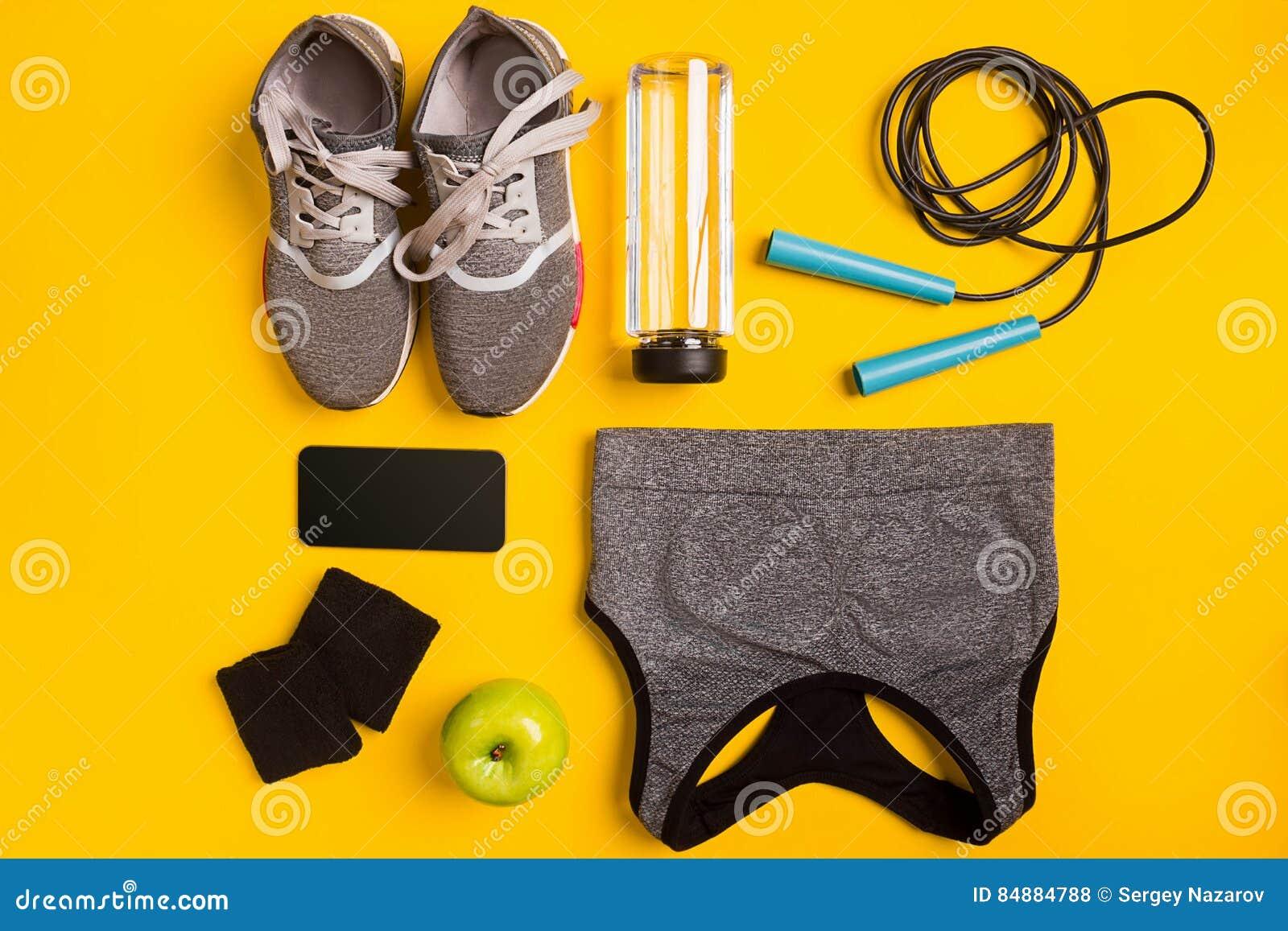 Accesorios de la aptitud en un fondo amarillo Las zapatillas de deporte, la botella de agua, la manzana y el deporte rematan