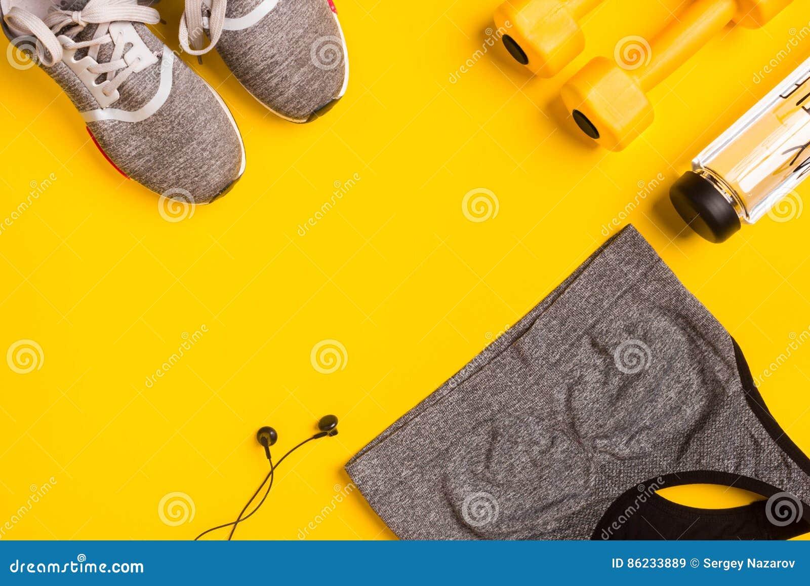 Accesorios de la aptitud en un fondo amarillo Las zapatillas de deporte, la botella de agua, los auriculares y el deporte rematan