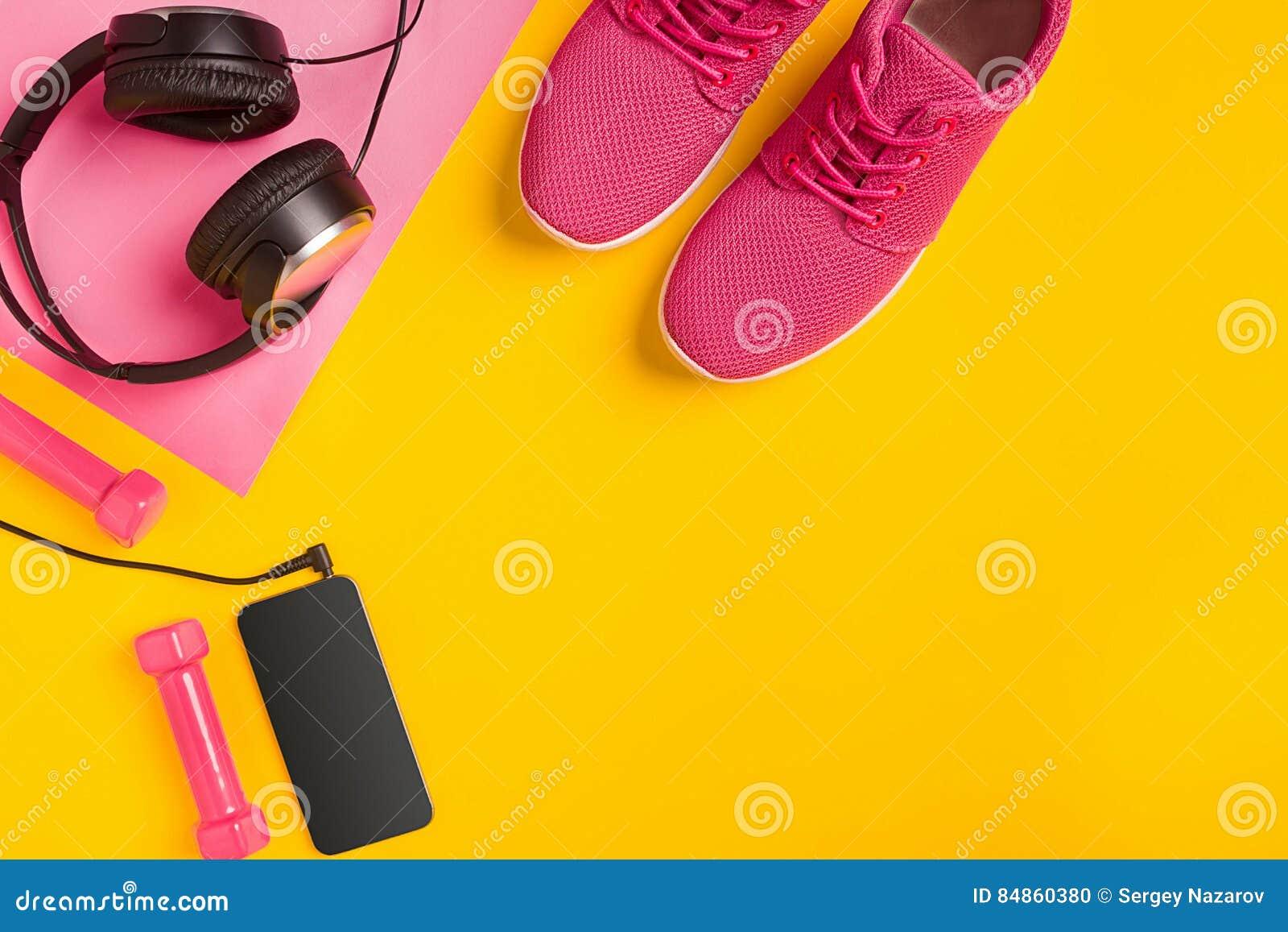 Accesorios de la aptitud en un fondo amarillo Zapatillas de deporte, botella de agua, auriculares y pesas de gimnasia