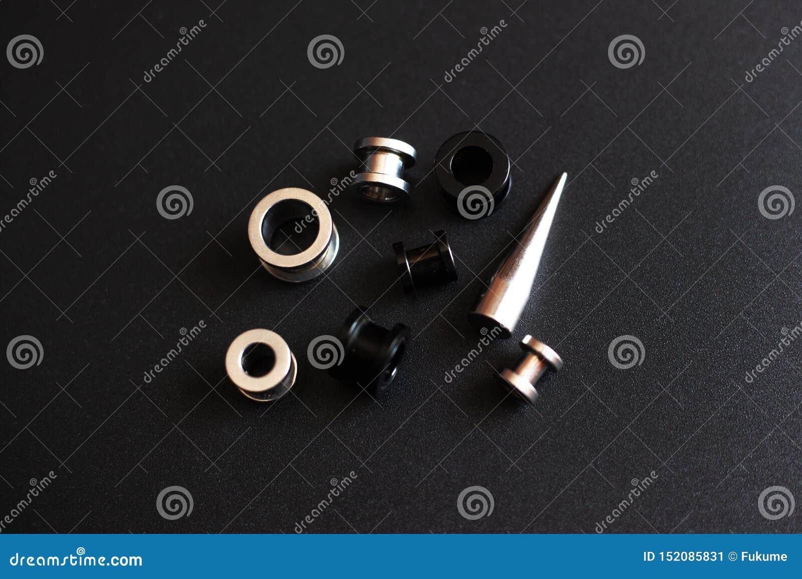 Accesorios de perforación en una joyería inoxidable del metal del fondo negro para los amantes de la puntura